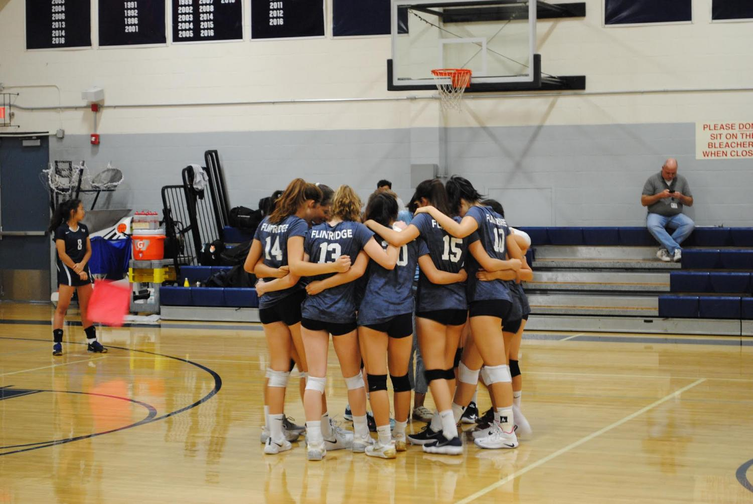 The girls' volleyball team huddles during the match.