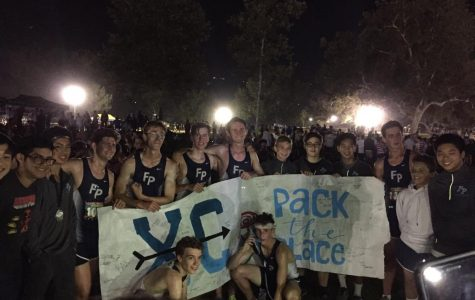 Boys' Cross Country holding the Pack the Place banner after their meet.