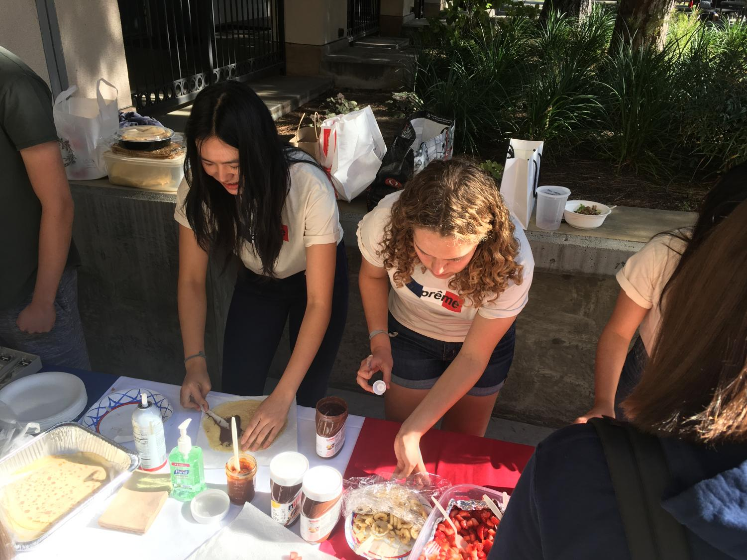 Chloe Chanren '19 and Katya Besch '20 make crepes for the crepe sale.