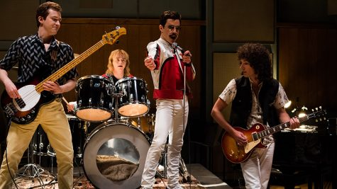 Joe Mazzello (John Deacon), Ben Hardy (Roger Taylor), Rami Malek (Freddie Mercury), and Gwilym Lee (Brian May) star in Bohemian Rhapsody.