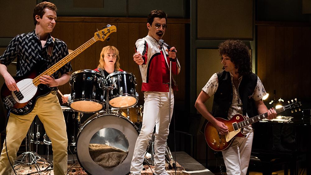 Joe Mazzello (John Deacon), Ben Hardy (Roger Taylor), Rami Malek (Freddie Mercury), and Gwilym Lee (Brian May) star in Bohemian Rhapsody.