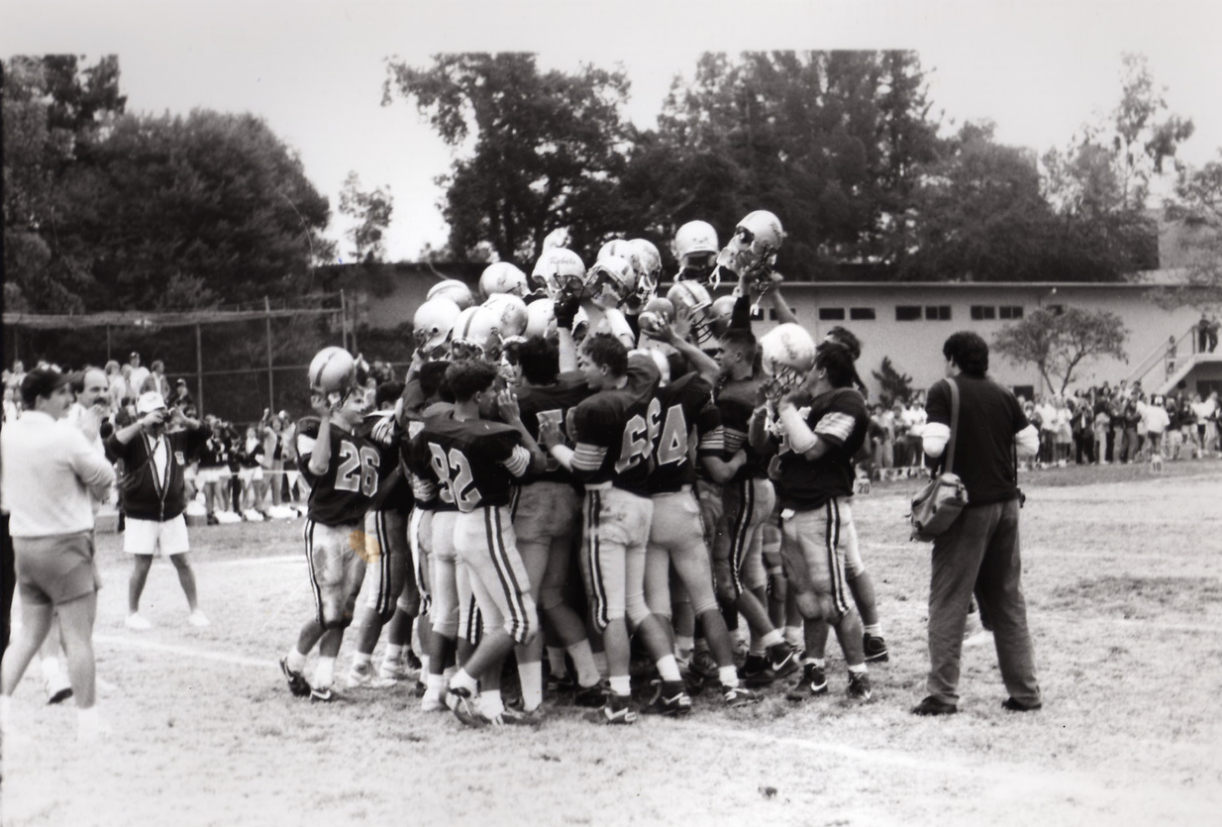 Rebel football players meet in a huddle in this archival photo from the 1980s.