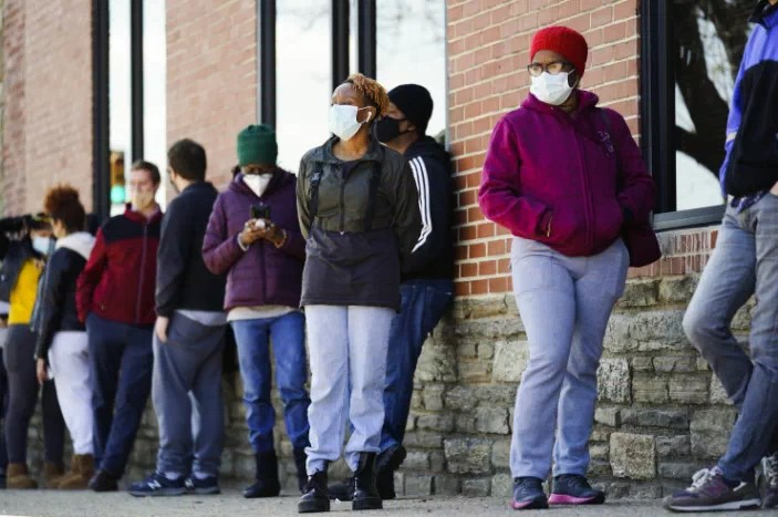 People wait in a line for COVID-19 vaccines at a site in Philadelphia, PA on Monday, March 29, 2021